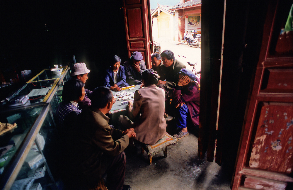 Locals play a game of dominoes in the doorway of a shop in southern China's Yunnan province.