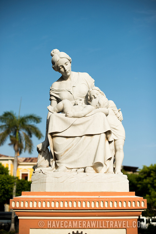 """A statue devoted to motherhood in Parque Central. The inscription reads """"Mother of all devotion and love."""" Parque Central is the main square and the historic heart of Granada, Nicaragua."""