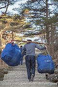 Rear view of a male porter carrying hotel laundry, Huangshan Mountain Range, Anhui Province, China