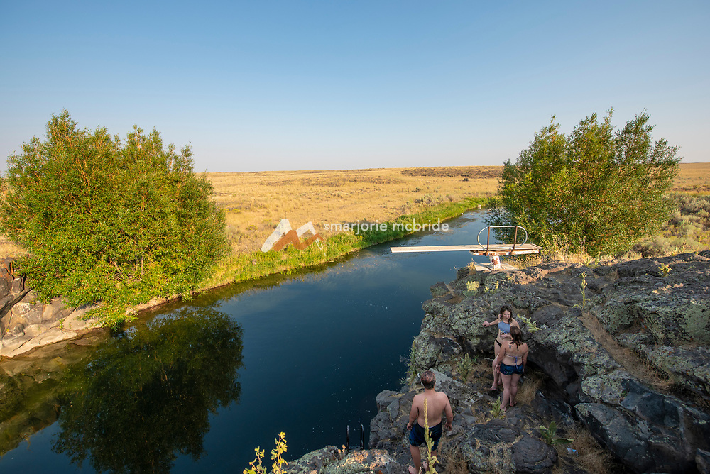 Teens on the cliffs at the Ledges swimming hole in Richfield, Idaho.