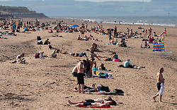 Portobello, Scotland, UK. 29 May 2020. Sunshine and temperatures of 23C at Portobello beach and promenade brought crowds of people outdoors. The relaxed covid-19 lockdown rules announced by the Scottish Government yesterday allows the public to sunbathe.  Iain Masterton/Alamy Live News