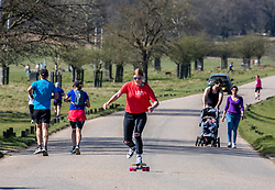 © Licensed to London News Pictures. 05/04/2020. London, UK. Walkers and skaters exercise in Richmond Park. Members of the public come out to exercise as temperatures reach 21c this weekend. Richmond Park seems quieter after the Government urged the public not to leave home during the fine weather as the Coronavirus crisis continues. Photo credit: Alex Lentati/LNP