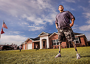 A wounded veteran stands outside of his home while his two daughters play in the background.