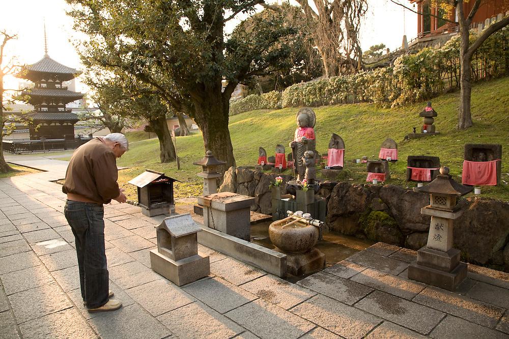 Asia, Japan, Honshu island, Nara, man praying at outdoor Buddhist shrine at Kofukuji Temple, a U.N. World Heritage Site