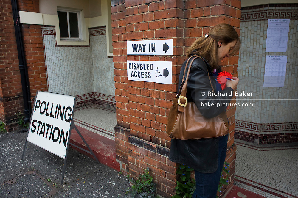 A teller attaches her red Labour Party rosette on Britain's general election day at St. Saviour's Church, Herne Hill SE24, south London. Her job is to record the election numbers of those about to vote, making surte that her political colleagues don't drop more literature in to that address, now that the occupants have voted. The two other parties also have their own volunteer tellers.