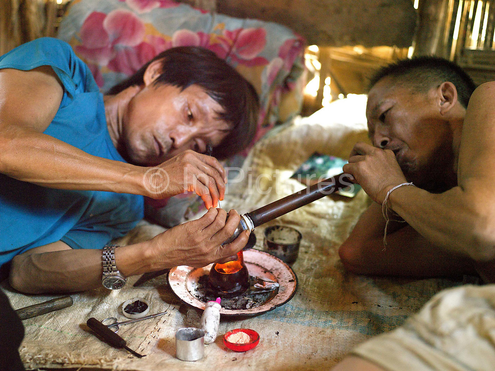 Two Hmong ethnic minority men smoke opium at home in Lao PDR. Opium addicts are usually adult males. By taking opium, they lose the energy to work hard which leaves heavy tasks to women and children which then impoverishes the entire household. As recently as 1998, Lao PDR was the third largest illicit opium poppy producer in the world.  From 1998 to 2005, opium poppy cultivation in Lao PDR was reduced by 93 per cent.  In more remote areas where cash crops are not viable, surveys from UNODC have shown that between 2008 and 2012 the area under opium poppy cultivation has more than tripled. Although in 2013 the area of poppy fields in the country has again fallen, the number of regular opium users was still estimated at between 14,000 to 15,000 in the 10 northern provinces.