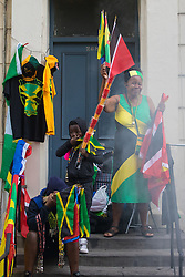 London, August 29th 2016. As smoke from a jerk chicken barbecue drifts along Ladbroke Grove a woman sell flags and trinkets during day two of Europe's biggest street party, the Notting Hill Carnival.