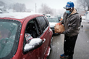 23 NOVEMBER 2020 - DES MOINES, IOWA: A volunteer hands a bag of food to a motorist in line during a Thanksgiving food distribution at a park in Des Moines during a snowstorm. The food distribution was organized by Urban Dreams, a community empowerment NGO in central Des Moines, and the NAACP. The food was provided by Hy-Vee, a regional grocery store chain based in Des Moines. They had about 450 meals available. A spokesperson for Hy-Vee said the company was giving away more than 20,000 Thanksgiving meals this year. The Food Bank of Iowa said food insecurity in Des Moines has doubled since the start of the Coronavirus pandemic.   PHOTO BY JACK KURTZ