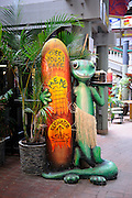 Large Gecko with surfboard advertising food for sale. Waikiki, Hawaii