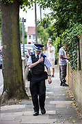 A Police Community Support Officer (PCSO) uses his radio while walking the beat in Enfield Town, Greater London, UK.