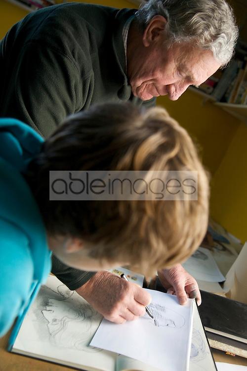 Grandfather teaching grandson to draw