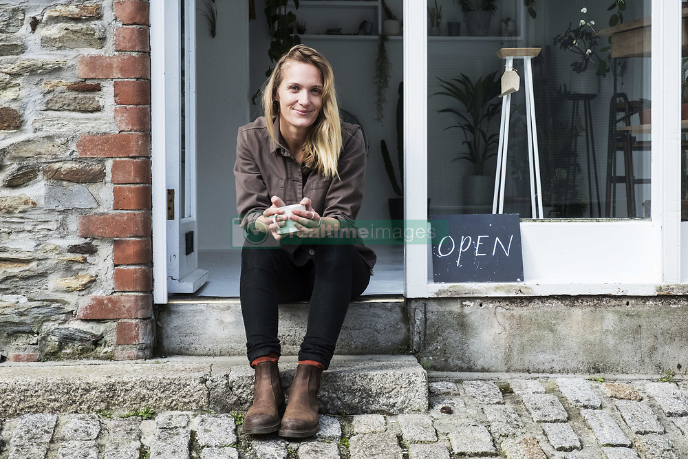 March 16, 2018 - Smiling female owner of plant shop sitting on steps outside her store, looking at camera. (Credit Image: © Mint Images via ZUMA Wire)
