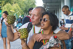 London, August 28th 2016. A couple drink out of pineapples during Family Day at Europe's biggest street party, the Notting Hill Carnival.