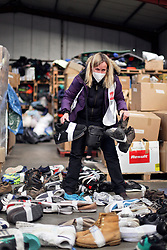 18 November 2020. Care4Calais - Calais, France.<br /> Claire Moseley, founder of the volunteer run migrant refugee charity Care4Calais searches through shoes at her charity's warehouse near Calais. Her charity provides meals, clothing, haircuts, charging stations for phones, hot drinks, tents, blankets and a wide range of goods and services to help migrant refugees struggling to survive on the streets of Calais where they are continually harassed and moved on by authorities. <br /> Photo©; Charlie Varley/varleypix.com