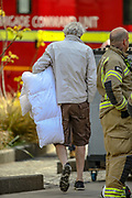 London, Britain, May 7, 2021 —  A resident is seen holding a blanket whilst walking around the neighbourhood after Firefighters tackled a blaze in a 19-storey block of flats in east London on Friday, May 7, 2021. (Photo/ Vudi Xhymshiti)