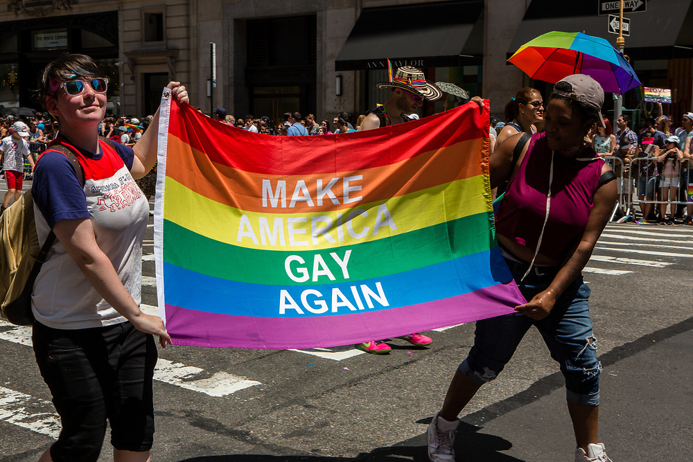 """New York, NY - 25 June 2017. New York City Heritage of Pride March filled Fifth Avenue for hours with groups from the LGBT community and it's supporters. Marchers carry a banner reading """"Make America gay again,"""" a dig at President Trump's campaign slogan."""