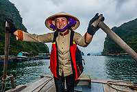 Local woman rowing a rowboat in Halong Bay, North Vietnam. The bay features 3,000  limestone and dolomite karsts and islets in various shapes and sizes sprinkled over 1,500 square kilometers. It offers a wonderland of karst topography. It is a UNESCO World Heritage Site.