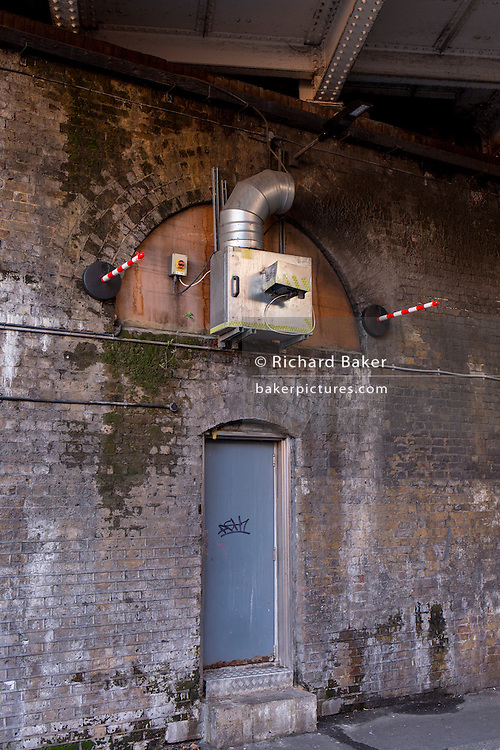 Damp walls, a doorway and new striped poles protruding from underneath a railway bridge, on 2nd March 2017, in Waterloo, London borough of Southwark, England.