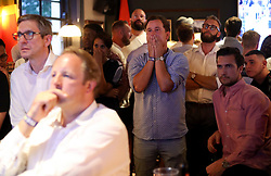 Dejected fans react as they watch the FIFA World Cup semi final match between Croatia and England at the William Hill Arms in London.