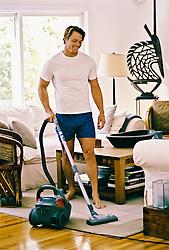 Man in boxer underwear vacuuming living room rug
