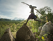 Young Hadza man on a hunt, with his bow and arrow. At the Hadza camp of Dedauko.