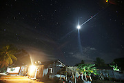 A modern Surui house at night with full moon<br /><br />An Amazonian tribal chief Almir Narayamogo, leader of 1350 Surui Indians in Rondônia, near Cacaol, Brazil, with a $100,000 bounty on his head, is fighting for the survival of his people and their forest, and using the world's modern hi-tech tools; computers, smartphones, Google Earth and digital forestry surveillance. So far their fight has been very effective, leading to a most promising and novel result. In 2013, Almir Narayamogo, led his people to be the first and unique indigenous tribe in the world to manage their own REDD+ carbon project and sell carbon credits to the industrial world. By marketing the CO2 capacity of 250 000 hectares of their virgin forest, the forty year old Surui, has ensured the preservation, as well as a future of his community. <br /><br />In 2009, the four clans and 25 Surui villages voted in favour of a total moratorium on logging and the carbon credits project. <br /><br />They still face deforestation problems, such as illegal logging, and gold mining which causes pollution of their river systems