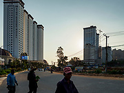 """13 FEBRUARY 2019 - SIHANOUKVILLE, CAMBODIA:  Cambodian laborers walk past the Xihu Resort Hotel in Sihanoukville. There are about 80 Chinese casinos and resort hotels open in Sihanoukville and dozens more under construction. The casinos are changing the city, once a sleepy port on Southeast Asia's """"backpacker trail"""" into a booming city. The change is coming with a cost though. Many Cambodian residents of Sihanoukville  have lost their homes to make way for the casinos and the jobs are going to Chinese workers, brought in to build casinos and work in the casinos.      PHOTO BY JACK KURTZ"""