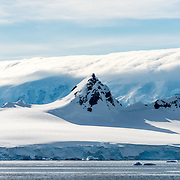 A steep peak rises above the surround mountain, while in the background clouds obscure an even taller mountain range in the Gerlache Strait on the Antarctic Peninsula.