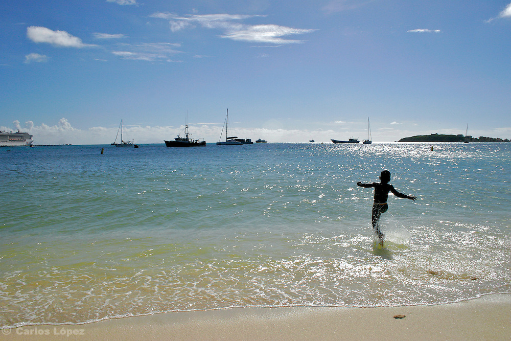 A boy is runing to the sea in a caribbean beach.