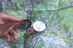 Hiker check route on map with Compass, Bavaria, Germany