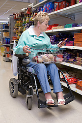 Woman wheelchair user shopping in a supermarket,