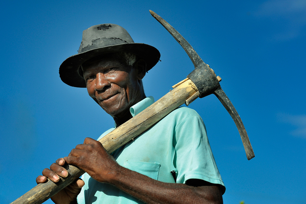 Surin Anold, 74, walks to his field in La Tremblay, Haiti, carrying a pick provided by the United Methodist Committee on Relief (UMCOR), which is working with earthquake survivors in the rural village to improve their agricultural production.