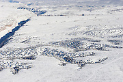 An aerial view of snow covered landscape with trees and river gorge.