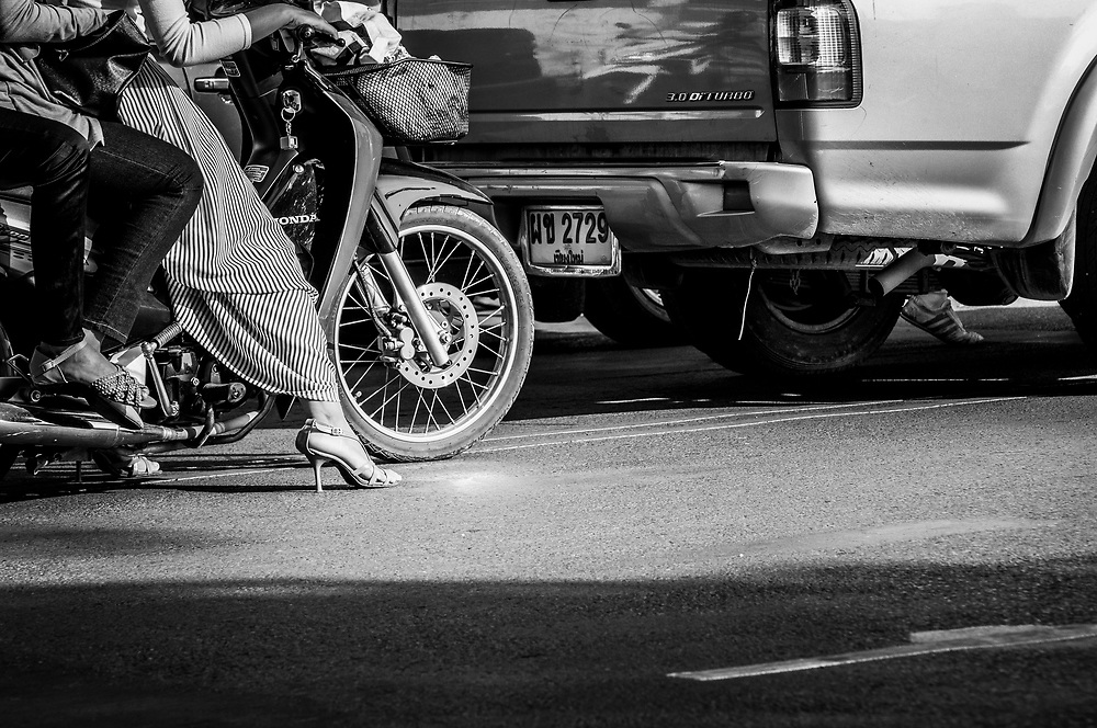 A woman wearing high-heel shoes waits in traffic behind the wheel of her motorbike in Chaing Mai, Thailand. (November 26, 2011)
