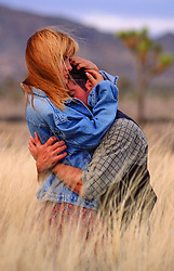 man and woman embracing in tall grass in Joshua Tree National Park, CA
