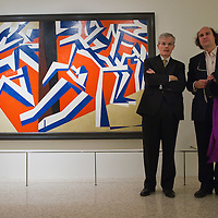 """VENICE, ITALY - JANUARY 28:  The Director of the Guggenheim Museum Philip Rylands (L) and the nephew of Futurist poet Marinetti, Leonardo Clerici (R) pose in front of the painting by David Bomberg """"The Mud Bath """" at the press launch of the Vorticist exhibition on January 28, 2011 in Venice, Italy. The Vorticists: Rebel Artists in London and New York, 1914-1918, is the first exhibition devoted to Vorticism to be presented in Italy will be open at the Peggy Guggenheim Collection from  January 29 through May 15, 2011."""