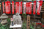 A statue of Hotei, one of the Seven Gods of Fortune at the Toyokawa Inari Betsuin temple in Asakusa, Tokyo, Japan. The Buddhist temple is part of the Soto Zen sect and enshrines the deity Toyokawa Dakinishinten but also known for the thousands of fox statues.