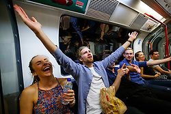 © Licensed to London News Pictures. 20/08/2016. London, UK. Tube passengers sing whilst travelling on the night tube service of Central line in London for the first time on 20 August 2016. Transport for London started a 24-hour Tube service on Victoria and Central lines as demand has soared over recent years, with passenger numbers on Friday and Saturday nights up by around 70 per cent since 2000. The plan was announced in November 2013 and intended to begin in September 2015, but strikes over pay delayed the start by nearly another year. Photo credit: Tolga Akmen/LNP