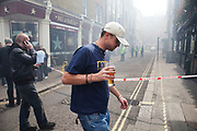 A drinker gulps back his beer in the smoke filled streets of Soho. A fire broke out on Dean Streen in Soho, Central London on Friday afternoon. The fire, in a five storey building in the heart of the city raged with firefighters struggling to get the blaze under control. In the nearby streets workers finishing early stood in the smoke filled streets having an end-of-the-week beer in the ghostly atmosphere.