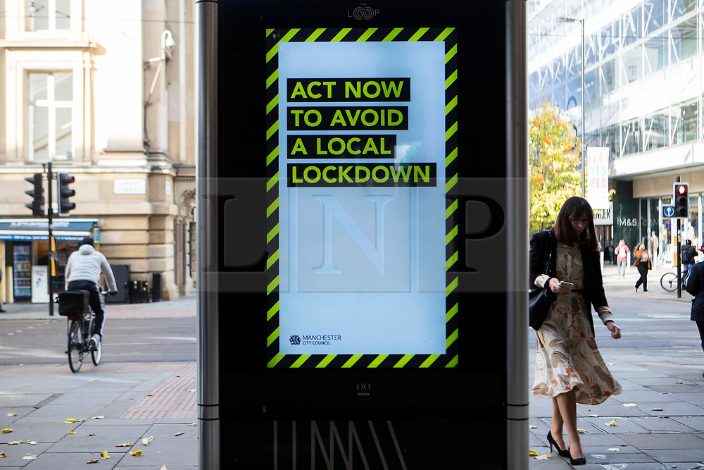 © Licensed to London News Pictures. 20/10/2020. Manchester, UK. A woman walks on a sign at Market Street in Manchester urging the public to take action to prevent a local lockdown. Manchester is expecting to be forced in to a Tier 3 lockdown unless a deal is agreed. Photo credit: Kerry Elsworth/LNP