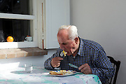 senior male person alone eating baked egg with bread