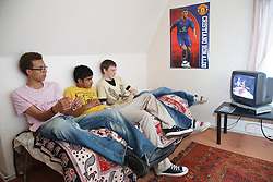 Groups of youths on sofa watching television.