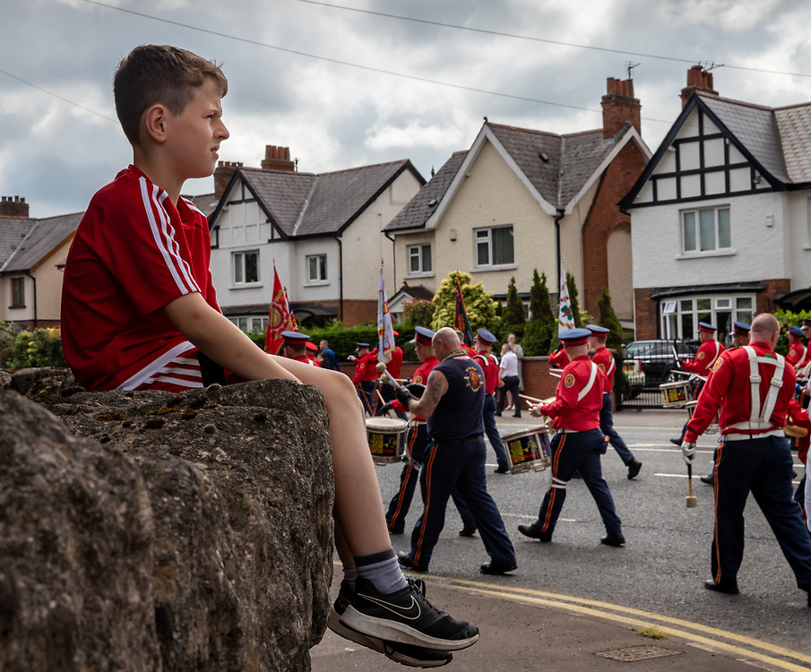 Young boy watching as the The Pride Of Ardoyne Flute Band parades through the streets of Belfast during the Orange March, 2021