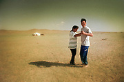 A couple dance in front of their yurt after eating a Marmot BBQ stew and drinking vodka. Near Bayan Nuur lake, Zavkhan Aimag, Mongolia.
