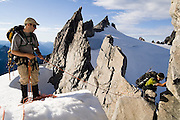 Jim Prager (l) and Brian Polagye tackle a difficult jagged ridge on a traverse of the Eldorado Icecap in North Cascades National Park, Washington.