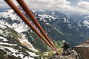 Climber Brian Polagye stands on a ledge as he rappels off the summit of Foggy Peak in the Monte Cristo area, Mount Baker-Snoqualmie National Forest, Washington on June 28, 2009.