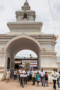 29 JUNE 2014 - DAN SAI, LOEI, THAILAND:  People walk into Wat Ponchai at the end of a merit making ceremony on the last day of the Ghost Festival. Phi Ta Khon (also spelled Pee Ta Khon) is the Ghost Festival. Over three days, the town's residents invite protection from Phra U-pakut, the spirit that lives in the Mun River, which runs through Dan Sai. People in the town and surrounding villages wear costumes made of patchwork and ornate masks and are thought be ghosts who were awoken from the dead when Vessantra Jataka (one of the Buddhas) came out of the forest. On the last day of the festival people participate in merit making ceremonies at the Wat Ponchai in Dan Sai and lead processions through town soliciting donations for the temple.   PHOTO BY JACK KURTZ