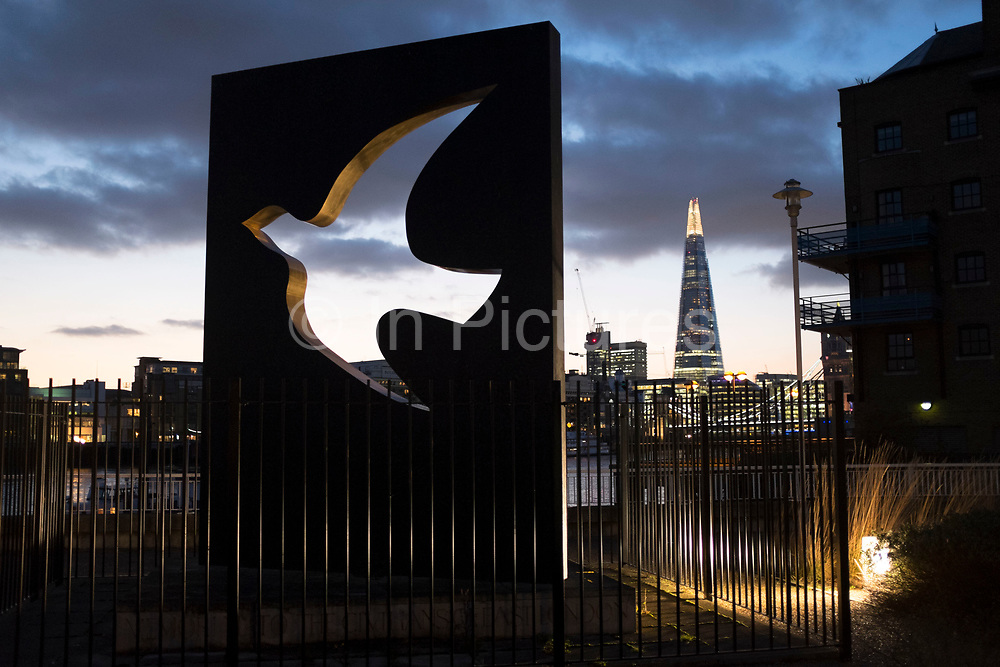View looking past the Peace Dove Sculpture, Hermitage Wharf Riverside Memorial Garden, to the skyline of Tower Bridge and The Shard in London, UK. One of the World's most famous cityscapes from Wapping towards this most iconic of skylines.