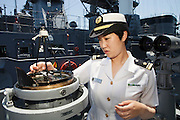 Mayu Kanzaki, the first female gunnery officer of Japan's MSDF, in front of the compass on the outdoors space of the bridge on the Yamagiri ship. <br /> Miho Ootani, the first woman destroyer captain of Japan's Marine Self Defence Forces (MSDF), on board the Yamagiri in Yokosuka army base near Tokyo.
