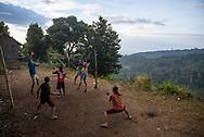 Bali, Indonesia - September 24, 2017: Several Balinese men play a game of volleyball on a rural hillside near Banjar, Bali.